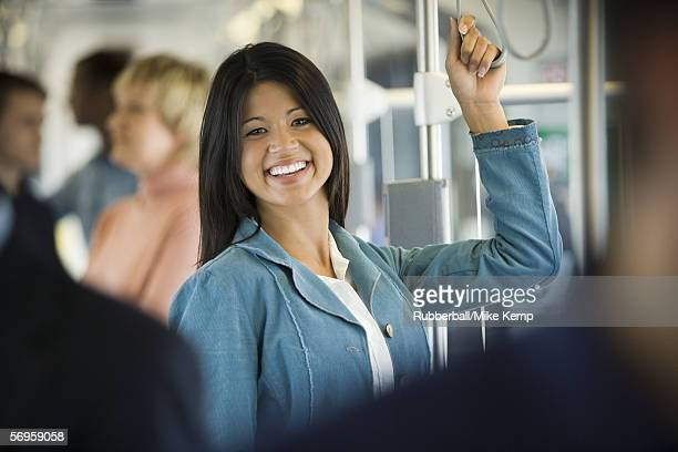 Portrait of a young woman standing in a passenger train