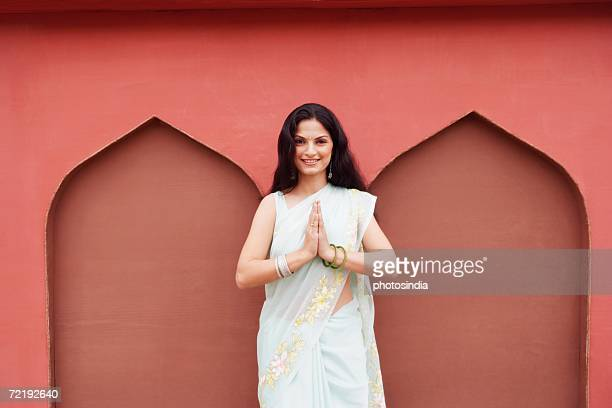 portrait of a young woman standing in a prayer position and smiling - prayer pose greeting bildbanksfoton och bilder