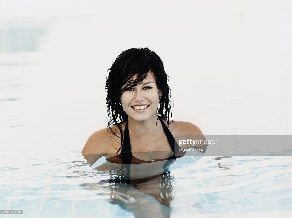 Portrait of a Young Woman Standing in a Swimming Pool : Stock Photo