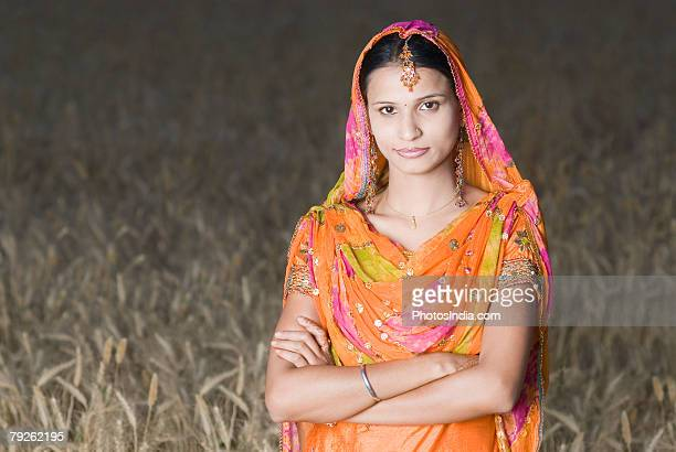 Portrait of a young woman standing in a wheat field