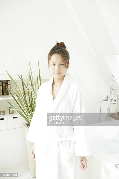 Portrait of a young woman standing in front of a bathtub