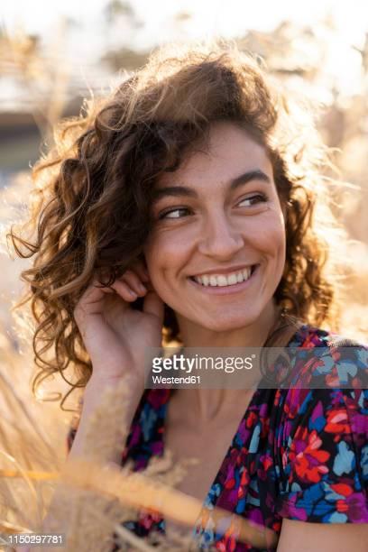portrait of a young woman standing in meadow, laughing - braunes haar stock-fotos und bilder