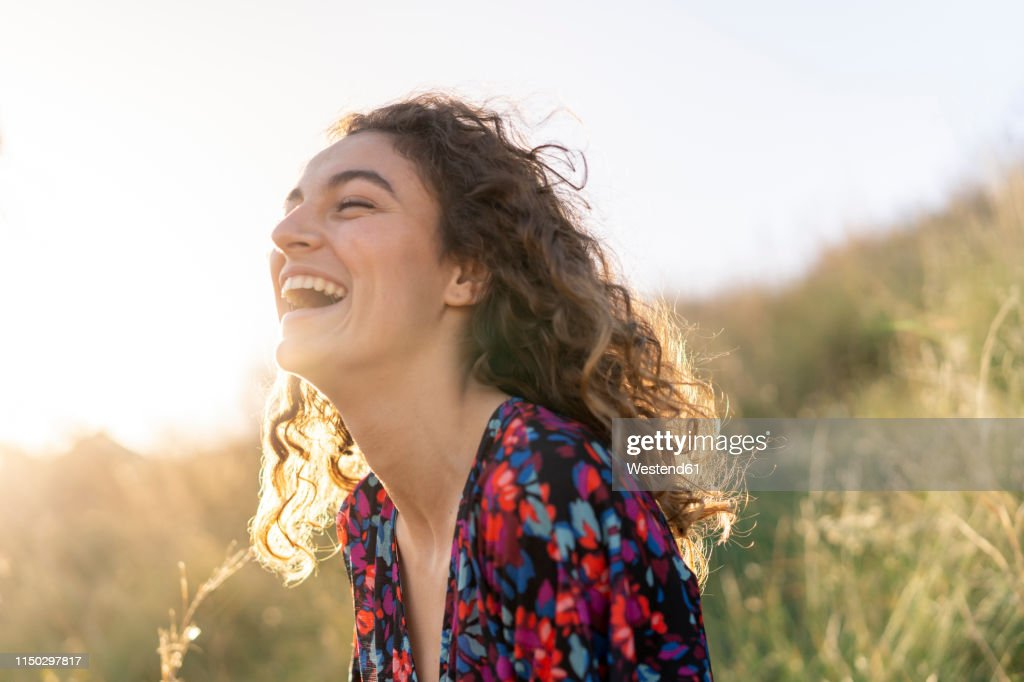 Portrait of a young woman standing in meadow, laughing : Foto de stock