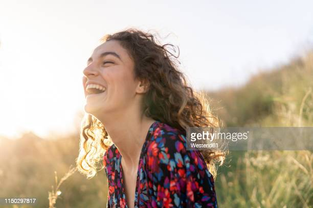 portrait of a young woman standing in meadow, laughing - contente imagens e fotografias de stock