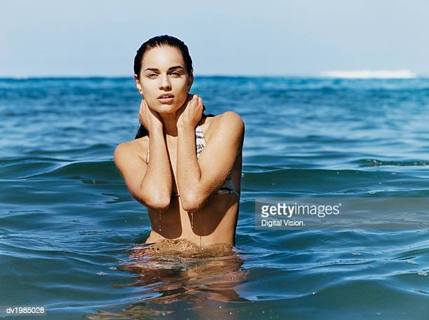 portrait of a young woman standing in the sea - bikini top stock pictures, royalty-free photos & images