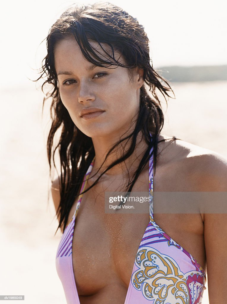 Portrait of a Young Woman Standing on a Beach and Wearing a Swimming Costume : Stock Photo