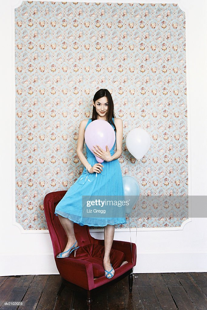 Portrait of a Young Woman Standing on an Armchair and Holding a Balloon : Stock Photo