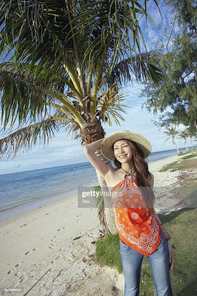 Portrait of a Young Woman Standing on the Beach by a Palm Tree : Stock Photo