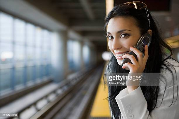 Portrait of a young woman talking on a mobile phone at a subway station