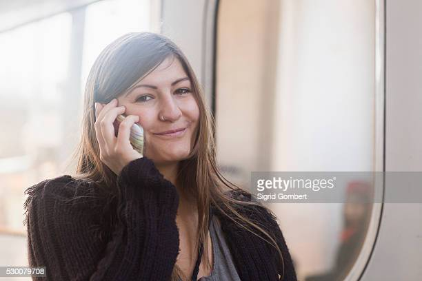 portrait of a young woman talking on mobile phone in front of a train, freiburg im breisgau, baden-w��rttemberg, germany - sigrid gombert fotografías e imágenes de stock