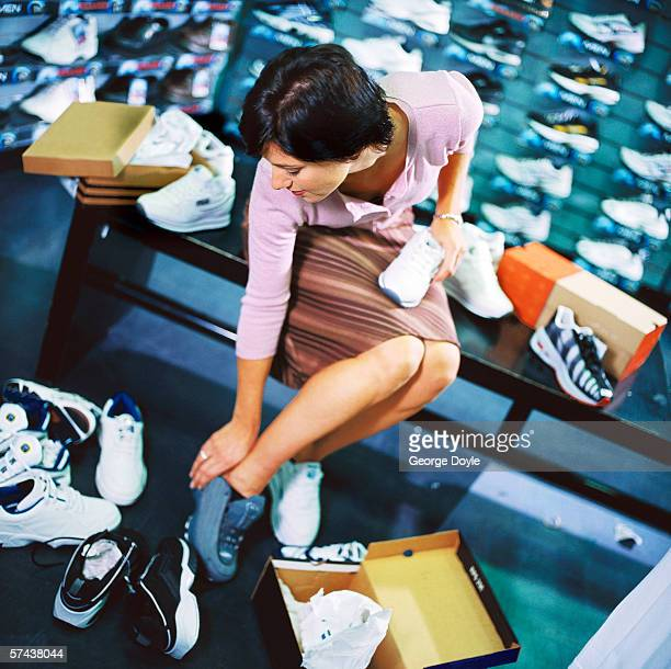 portrait of a young woman trying on shoes at a shoe store
