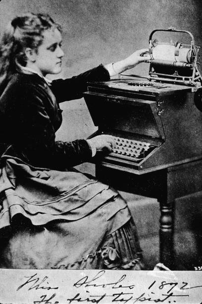 Portrait of a young woman typing on an early typewriter,...
