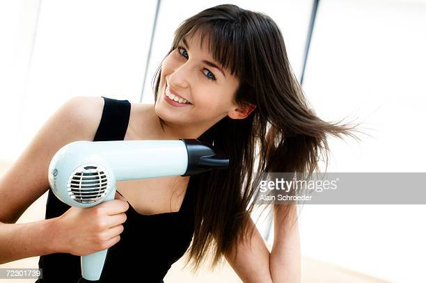 Portrait of a young woman using a hair drier
