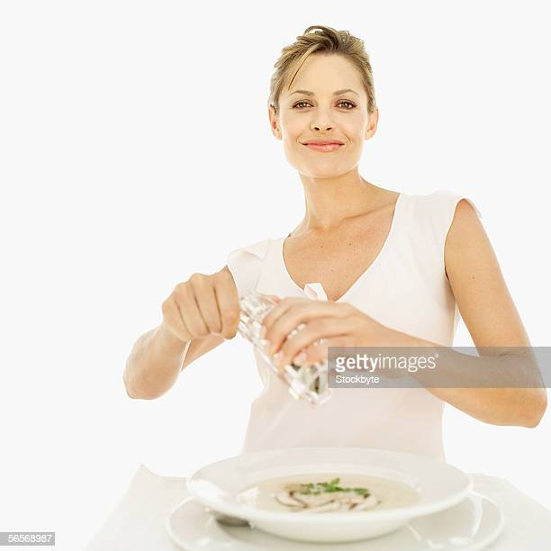 portrait of a young woman using a pepper mill over a bowl of mushroom soup