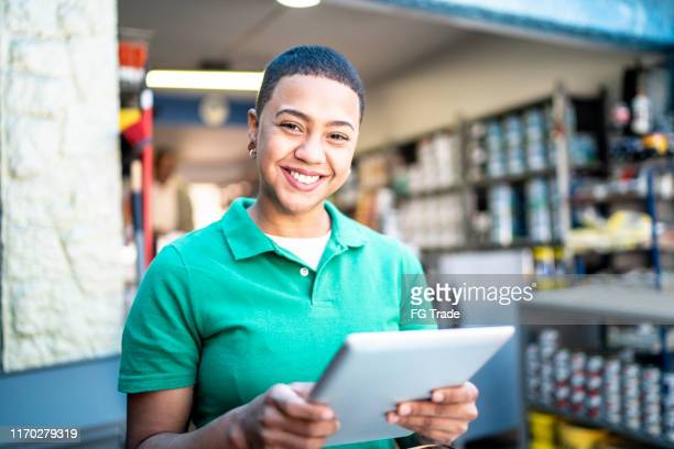 portrait of a young woman using computer digital tablet in a paint store - construction material stock pictures, royalty-free photos & images