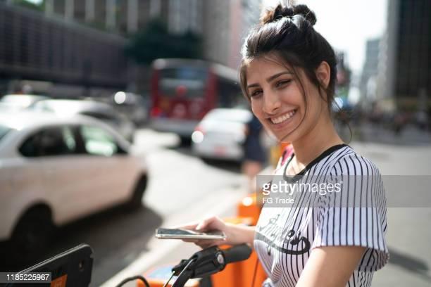 retrato de uma mulher nova que usa o smartphone - coque cabelo para cima - fotografias e filmes do acervo
