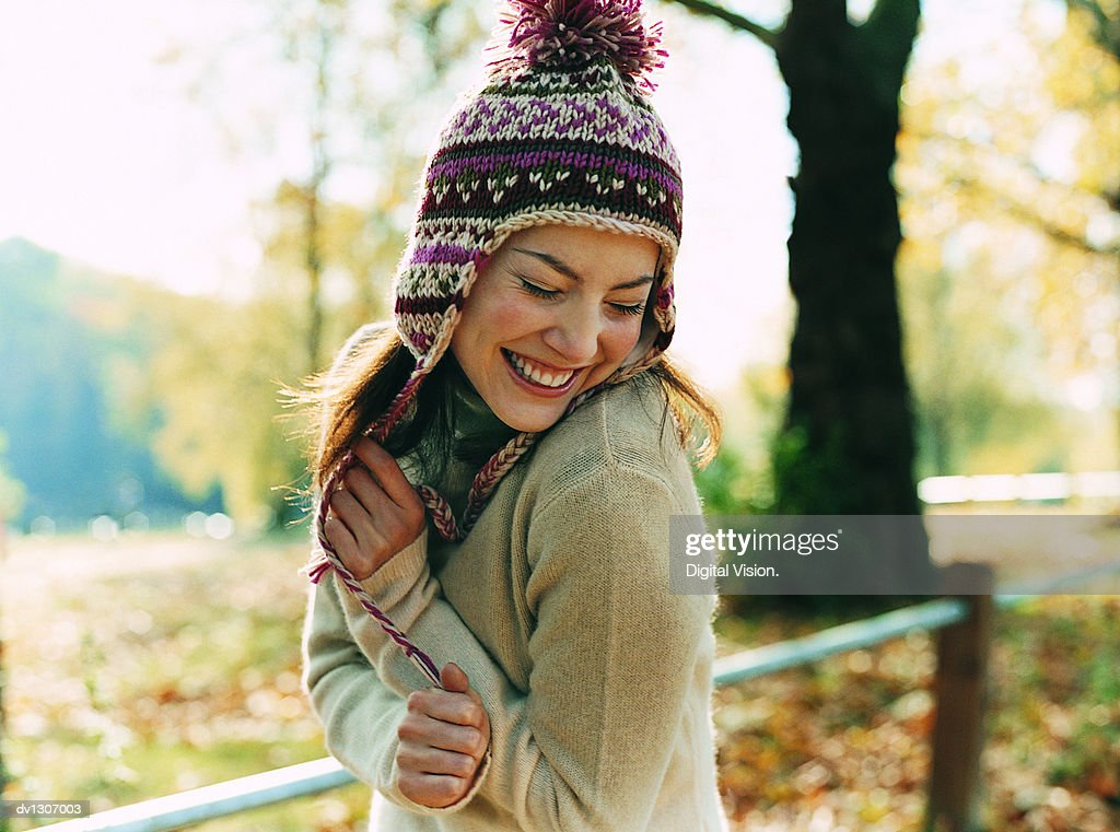 Portrait of a Young Woman Wearing a Bobble Hat Smiling With Her Arms in Front and Her Eyes Closed : Photo