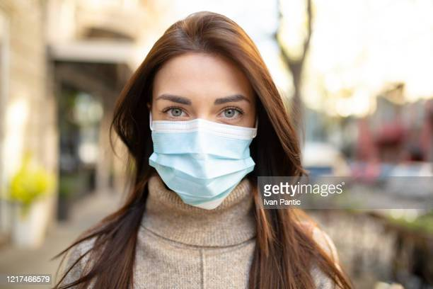 portrait of a young woman wearing a face mask - mascherina antipolvere foto e immagini stock