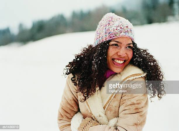 portrait of a young woman wearing a hat in the snow - abiti pesanti foto e immagini stock