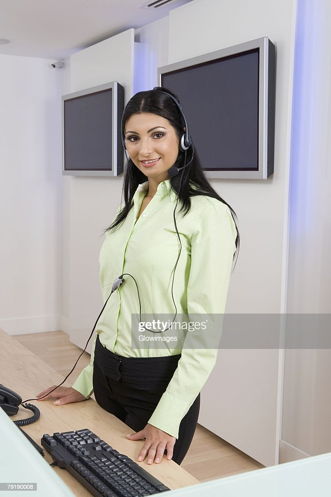 Portrait of a young woman wearing a headset and smiling : Foto de stock