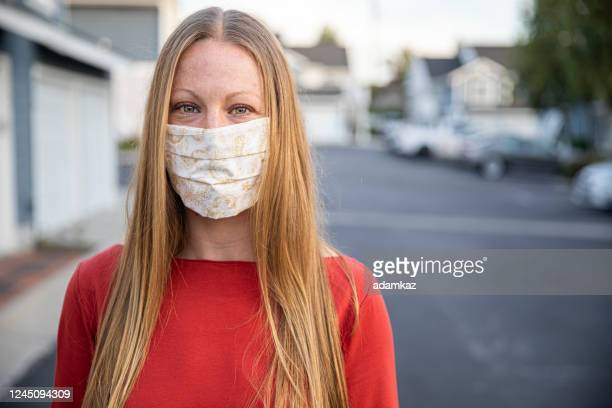 portrait of a young woman wearing a mask outdoors - adamkaz stock pictures, royalty-free photos & images
