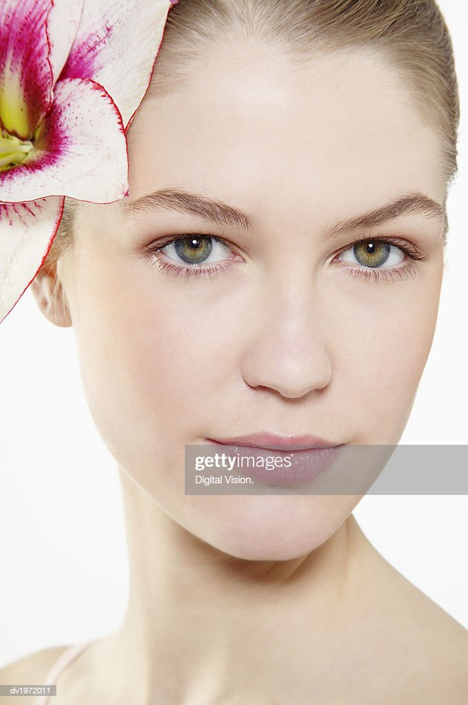 Portrait of a Young Woman Wearing a Single Flower in Her Hair : Stock Photo