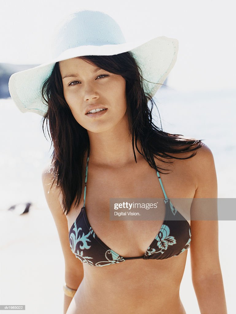 Portrait of a Young Woman Wearing a Sunhat and a Bikini Top Standing by the Sea : Stock Photo