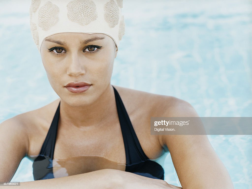 Portrait of a Young Woman Wearing a Swimming Cap Standing at the Edge of a Swimming Pool : Stock Photo