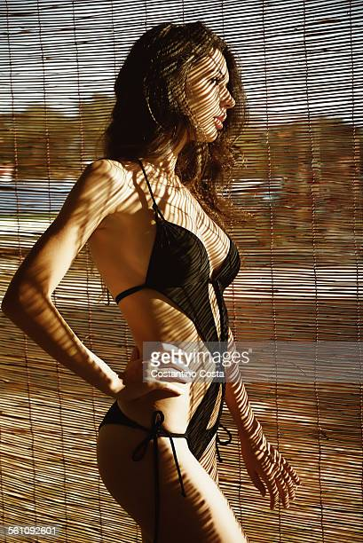 Portrait of a young woman wearing a swimming costume standing in front of a wicker screen on beach