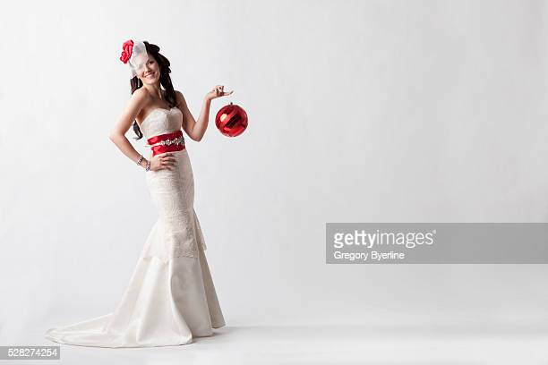 portrait of a young woman wearing a white strapless formal dress with red accessories against a white background; nashville tennessee united states of america - fascinator stock pictures, royalty-free photos & images