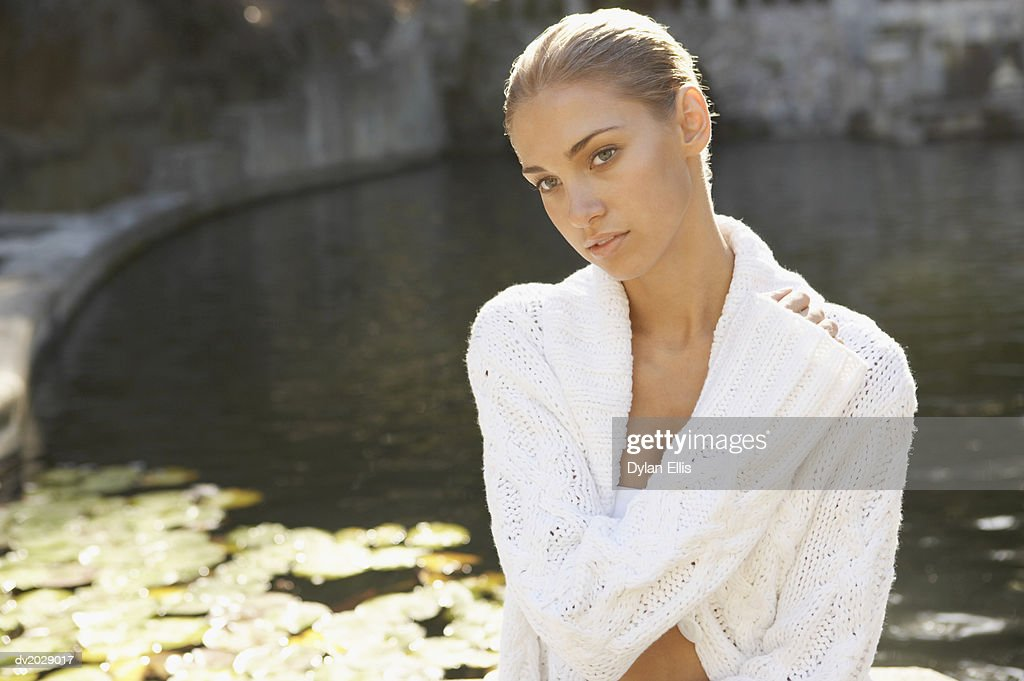 Portrait of a Young Woman Wearing a Woolen Cardigan by a Lake : Stock Photo