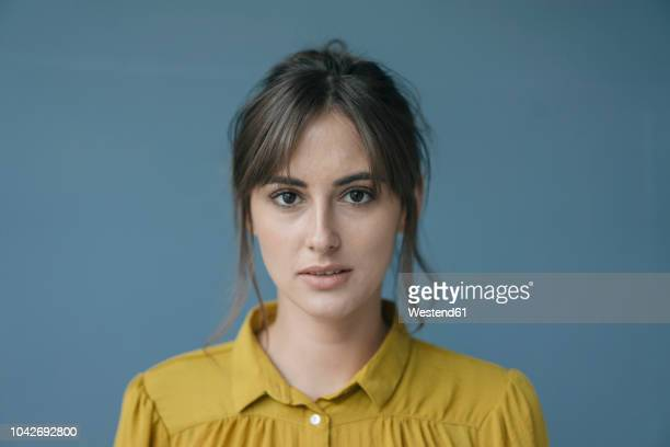 portrait of a young woman wearing a yellow blouse - porträt stock-fotos und bilder