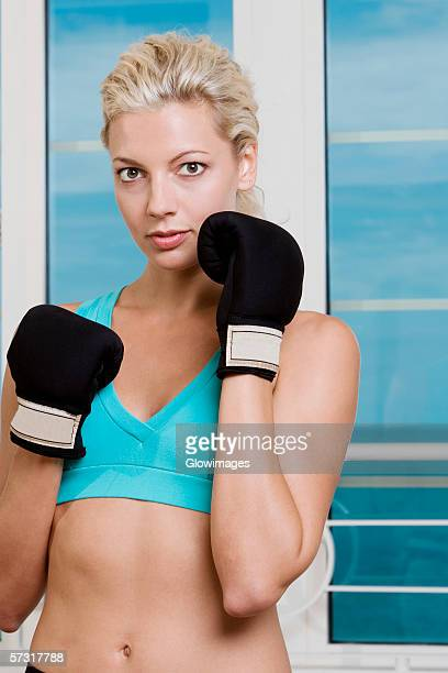 portrait of a young woman wearing boxing gloves - belly punching stock pictures, royalty-free photos & images