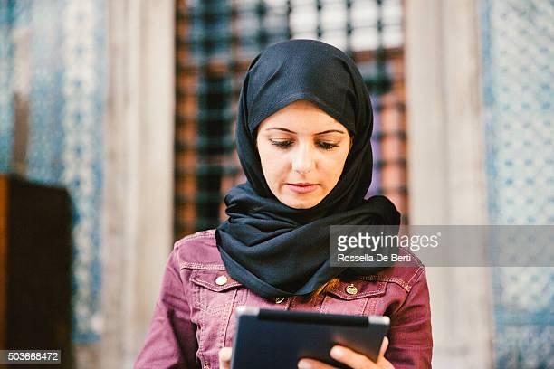Portrait d'une jeune femme avec foulard à l'aide de la tablette à l'extérieur