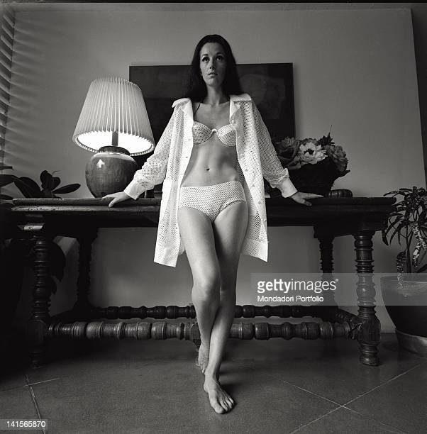 Portrait of a young woman wearing her lingerie in a Western style furnished house Mexico October 1968