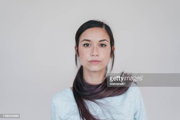 portrait of a young woman wearing her ponytail wrapped around her neck - ponytail stock pictures, royalty-free photos & images
