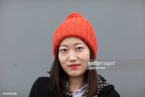 portrait of a young woman wearing orange hat - sigrid gombert stock pictures, royalty-free photos & images
