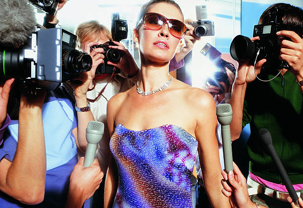 Portrait of a Young Woman Wearing Sunglasses and an Evening Gown Being Photographed by Paparazzi
