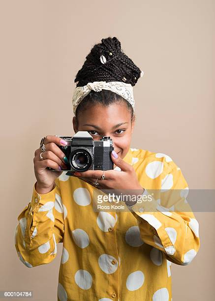 Portrait of a young woman with a camera.