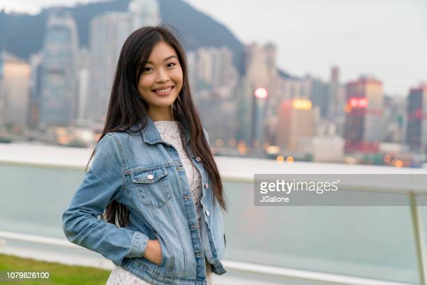 Portrait of a young woman with a Hong Kong skyline backdrop