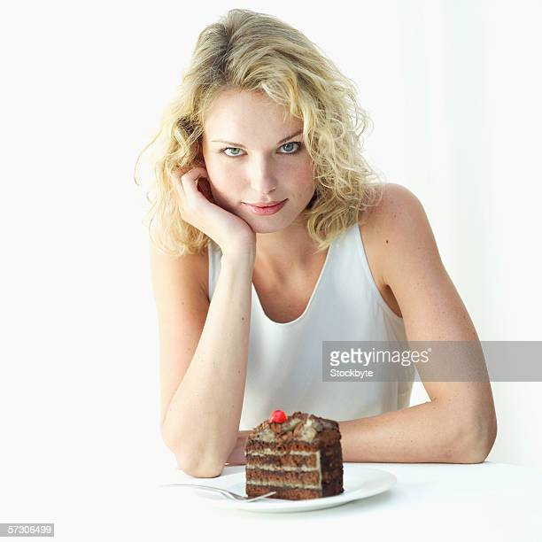 Portrait of a young woman with a piece of chocolate cake on a plate