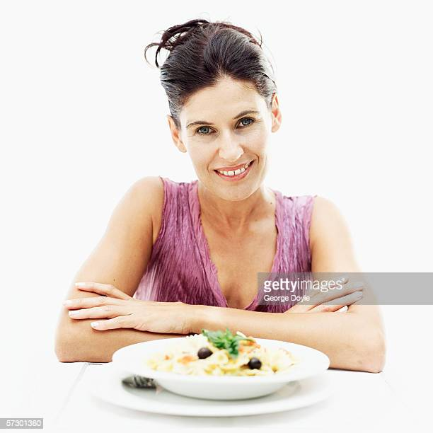 portrait of a young woman with a plate of pasta - mid adult women stock pictures, royalty-free photos & images