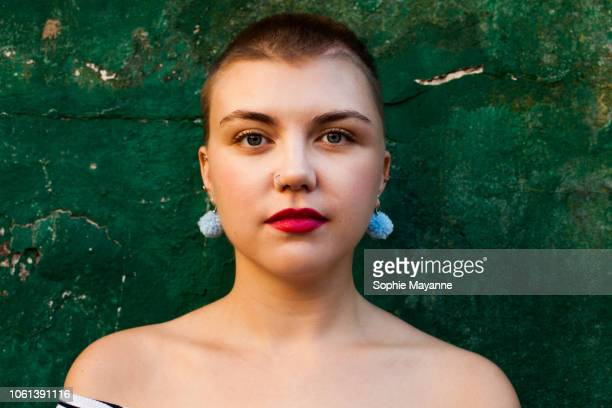 A portrait of a young woman with a shaved head
