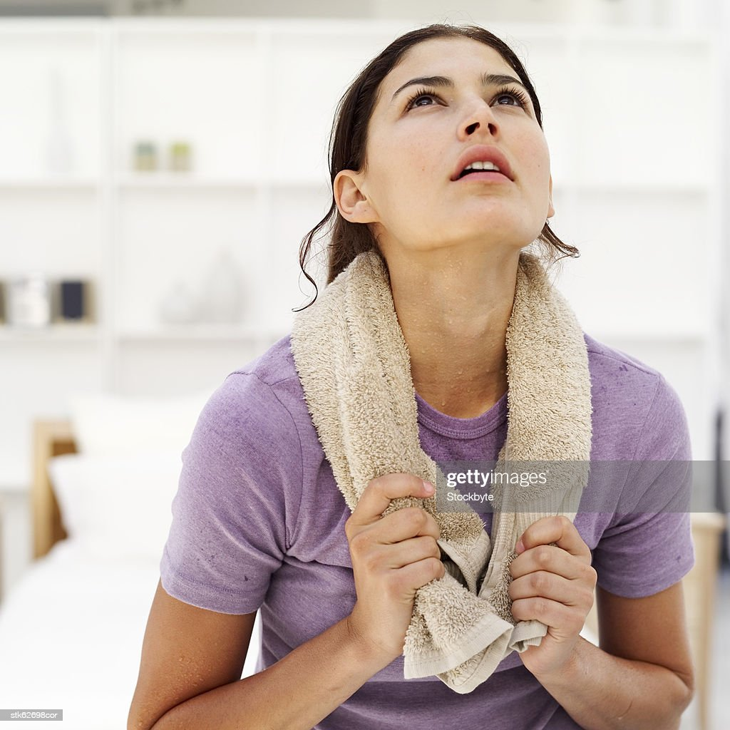 portrait of a young woman with a towel around her neck looking up : Stock Photo
