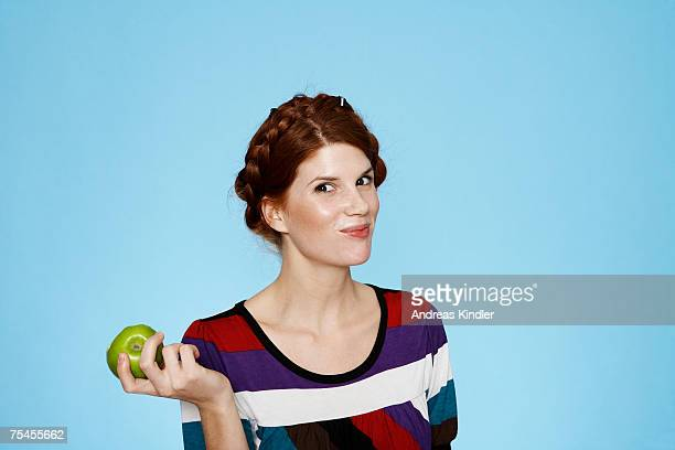 Portrait of a young woman with an apple in her hand.