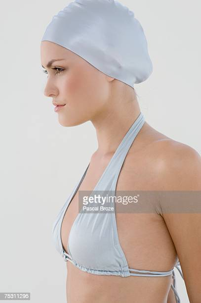 portrait of a young woman with bikini and swimming cap, view in profile - badmuts stockfoto's en -beelden