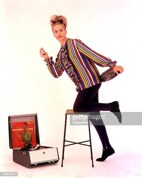 1962 A portrait of a young woman with blonde hair who is wearing a fashionable multicoloured stripy top with black trousers She is kneeling on a...
