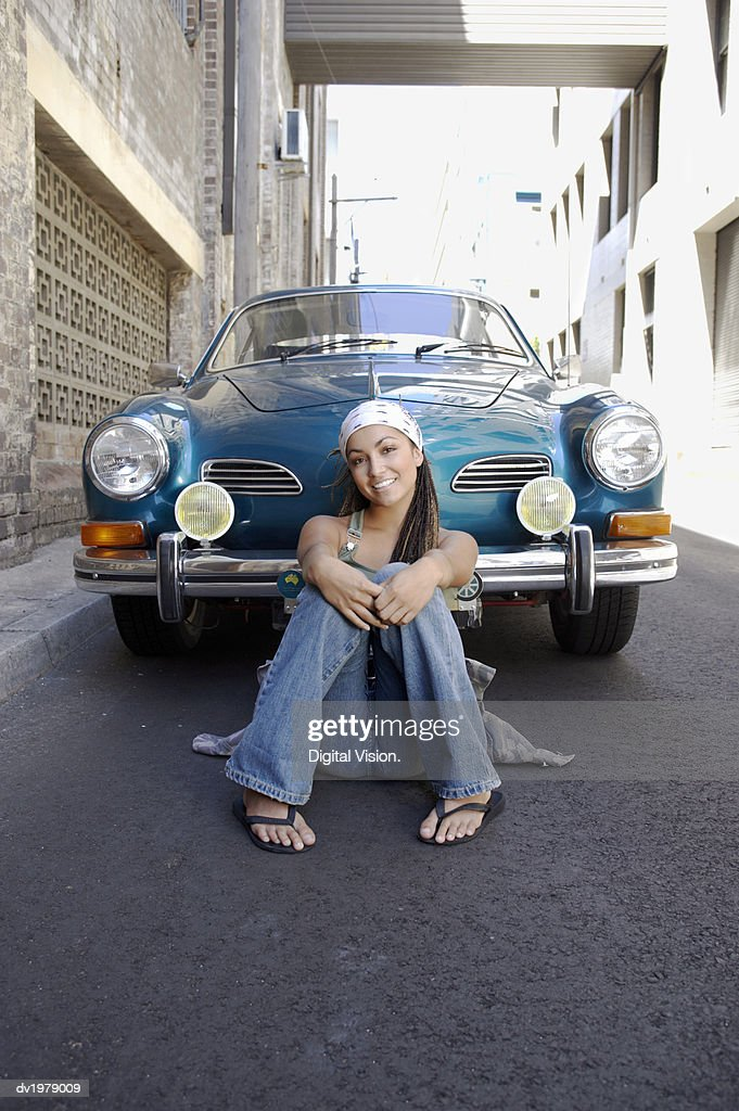 Portrait of a Young Woman With Dreadlocks Leaning Against a Classic Blue Car : Stock Photo