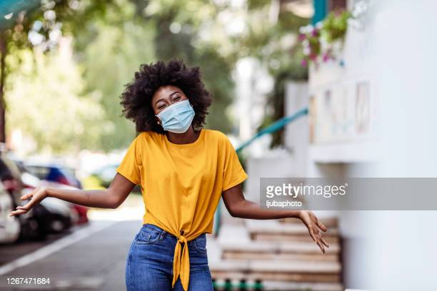 portrait of a young woman with face mask outdoors in the city - respiratory disease stock pictures, royalty-free photos & images