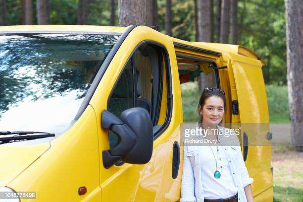 Portrait of a young woman with her camper van in a forest